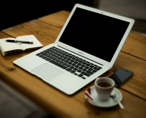 Laptop, Cafetasse und Schreibblock